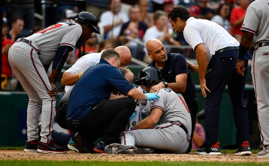 Charlie Culberson (8) is looked at by Braves medical staff after being hit with a pitch during the seventh inning.