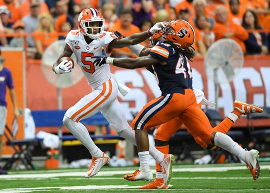 Clemson wide receiver Tee Higgins (5) grabs the face mask of Syracuse linebacker Lakiem Williams while running with the ball.