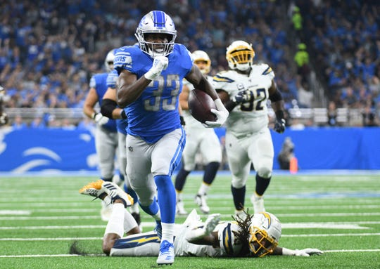 Detroit Lions running back Kerryon Johnson gets past the Los Angeles Chargers defense and scores a touchdown in the first half at Ford Field.