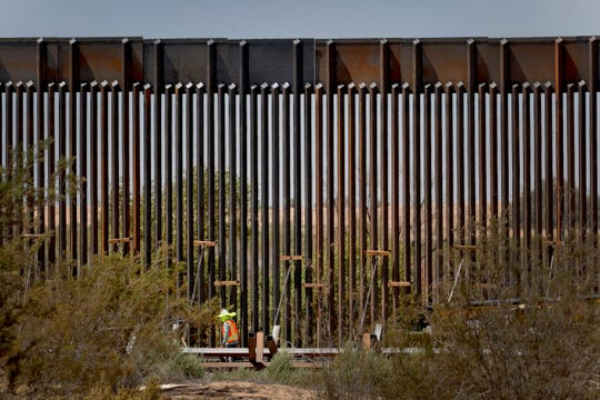 A government contractor walks beside a completed section of Pentagon-funded border wall along the Colorado River, Tuesday, Sept. 10, 2019 in Yuma, Ariz.