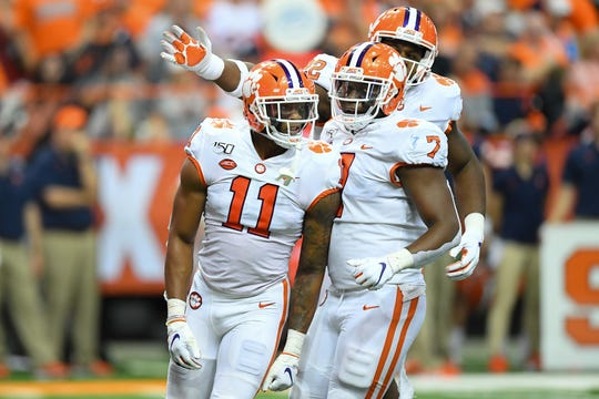 Clemson linebacker Isaiah Simmons (11) reacts to a defensive play with teammates defensive end Justin Mascoll (7) and defensive tackle Xavier Kelly (back) against Syracuse.