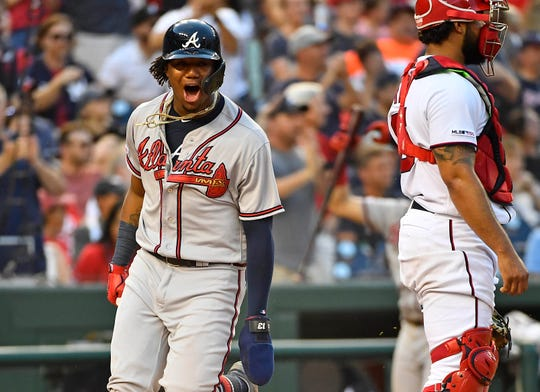 Center fielder Ronald Acuña Jr., left, celebrates after scoring a run against the Nationals during the seventh inning.