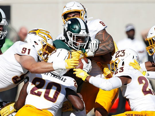 Michigan State running back Elijah Collins, center, meets a group of Arizona State defenders.