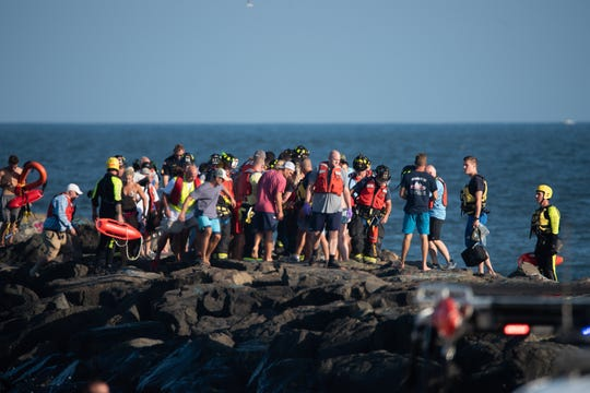 Rescuers help a fisherman who fell on a jetty at the Manasquan Inlet on Sunday, Sept. 15, 2019.