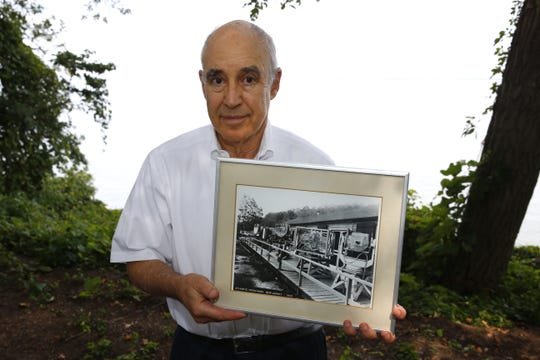 Josh Leinsdorf wants to commemorate the spot where radar was developed in Atlantic Highlands. Here he holds an old photo of the secret army lab along Bayside Drive.