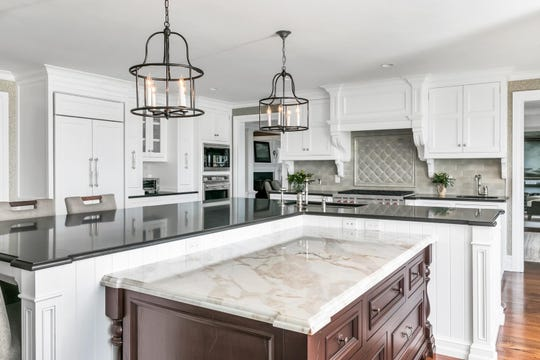 The gourmet kitchen features custom cabinetry and granite tops and center island