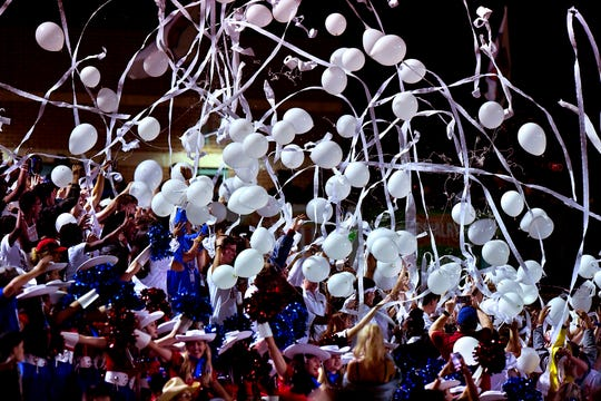 Cooper High School students throw balloons and toilet paper into the air during the second half of Friday's Crosstown Showdown football game against Abilene High.