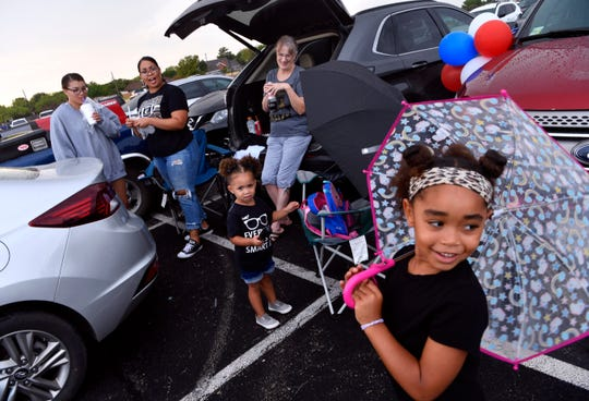 Ali Nelson, 5, twirls her umbrella as she and her 2-year-old sister Carter Player tailgate with family in the parking lot at Shotwell Stadium Friday. Fans of both Abilene and Cooper high schools tailgated together before the evening's Crosstown Showdown football game.