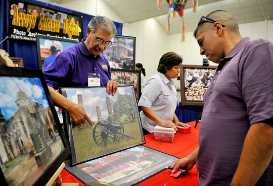 Owner of Arroyo Catclaw Digital Mike Hernandez, left, talks to Porfirio Bustillos, right, about digital imaging during the Business Mercado at the Abilene Civic Center in October 2012. has been named the Abilene Chamber of Commerce's Outstanding Citizen of the Year for 2019.