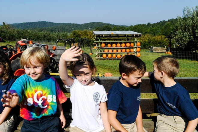 Christ School Episcopal School students wave to their fellow kindergarteners riding in another tractor trailer as they head to pick apples at Sky Top Orchard in Flat Rock September 12, 2019.