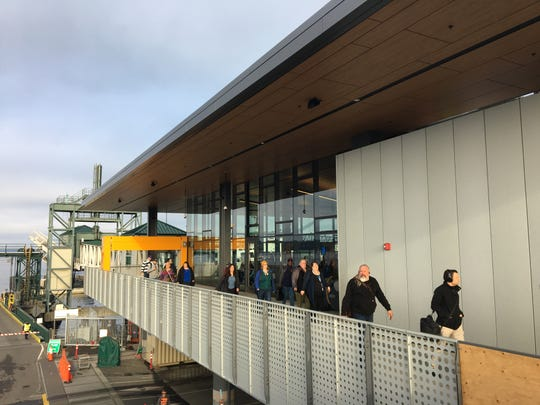 Morning commuters walk along the new ferry terminal building at Colman Dock on Monday.