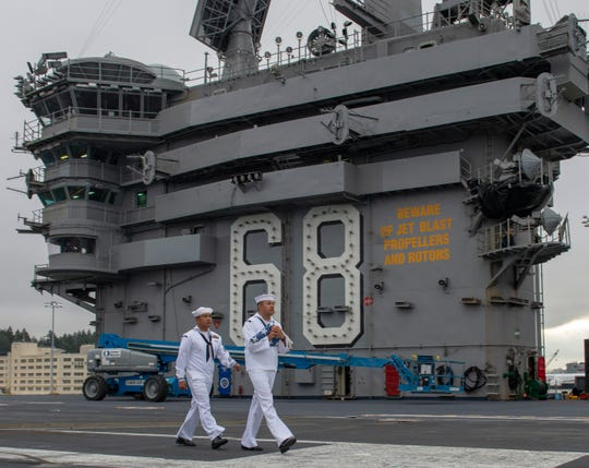 Aviation Boatswain's Mate (Handling) 1st Class Joeffrey Mamaril, left, from San Diego, and Aviation Ordnanceman 1st Class Ynocincio Martinez from Houston, march on the flight deck on the aircraft carrier USS Nimitz. Nimitz left Bremerton Monday.