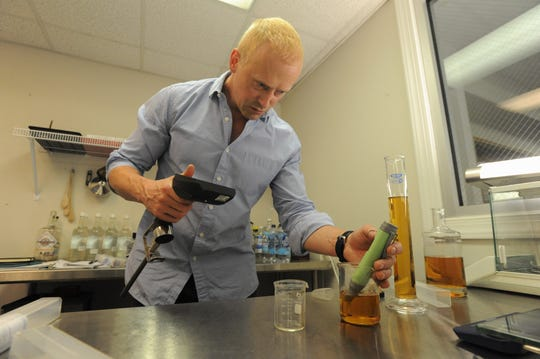 Chad Slagle checks proofs a batch of whiskey in his laboratory inside of Two Trees Distilling Co. The Black Mountain native, with his longtime friend Keith Mort, developed a technology that speeds up the aging process of whiskey.