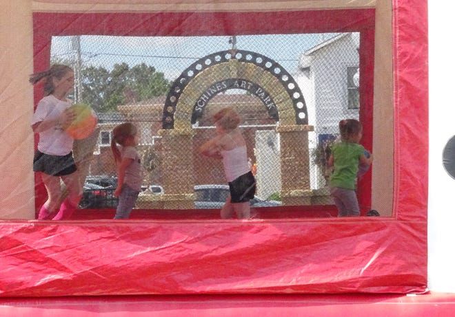 Children play in a bounce house set up in Schines Art Park in downtown Bucyrus during a Street Recovery event on Saturday afternoon.