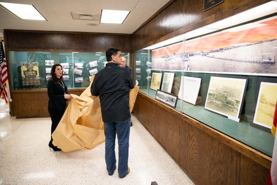 Nueces County Judge Barbara Canales and Nueces County Commissioner Brent Chesney unveil a display photos of Corpus Christi before the 1919 hurricane in the Nueces County Courthouse to commemorate the 100th anniversary of the 1919 storm on Monday, Sept. 16, 2019.