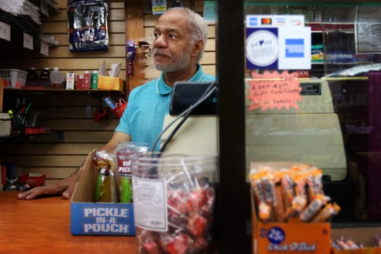 Reginald Stroud greets customers from behind the counter of Anybody's Dream, his convenience store in Northside. Stroud's store and home used to be on Walnut Street in Over-the-Rhine, but he had to move when developers bought his building.