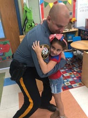 Sergeant Robert Ferreiro takes a moment to share a sweet hug with his daughter, Stella Ferreiro, a kindergarten student at Angelo L. Tomaso School on Patriot Day.