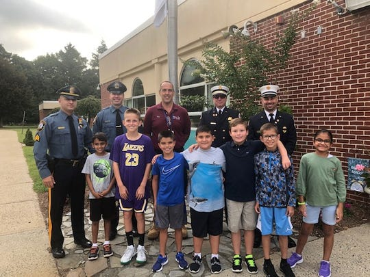 Special visitors from the Warren Township Police Department, Officer Sohler and Sergeant Ferreiro along with Warren Township Schools' employees,  Ronald Budis, US Army Veteran, and volunteer firefighters,  Donald Strickland and Michele Gonnella take a moment to stand with the grade 3 students Aayan Shah, William Hadfield, Christopher Molina, Nicholas Guerra, Constantin Bellman, Marc Shah and Mehreen Hussain who raised the American Flag on Wednesday, Sept. 11, at Angelo L. Tomaso School.