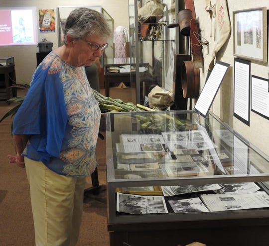 Carolyn Hays looks at items that are part of the 100th anniversary of the Ohio Farm Bureau Exhibit at the Johnson-Humrickhouse Museum. Hays donated several items from the family farm, her days in 4-H and the Tiverton Institute, an annual farmer education program still going today.