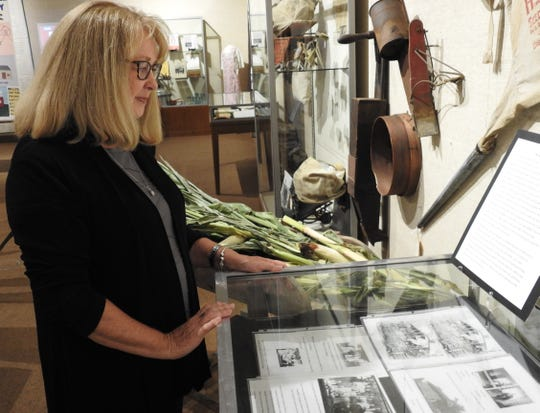 Phyllis Debnar looks at some items from the Pew and Lawrence families she donated to an exhibit at the Johnson-Humrickhouse Museum marking 100 years of the Ohio Farm Bureau.