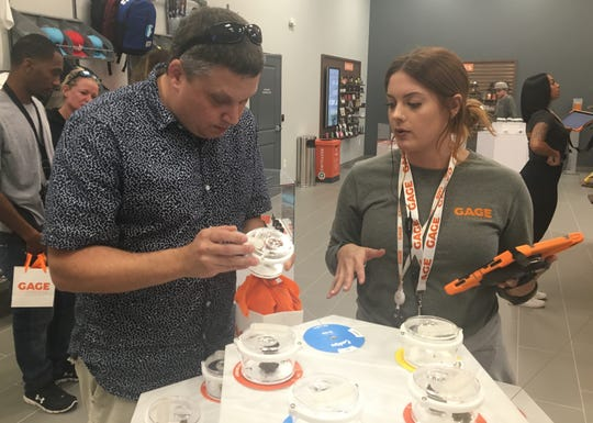 Senior product specialist Blake Paluch helps a customer look at a marijuana flower strain called Gellati at Gage, a medical marijuana dispensary at its grand opening in Ferndale, Saturday, Sept. 14, 2019.