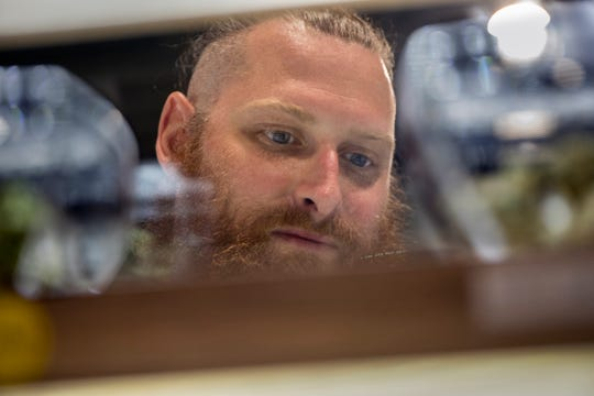 Andrew Zalewski, 33 of Warren looks at the different varieties of marijuana flower at Liv dispensary in Ferndale, Mich., Monday, Sept. 16, 2019.  He has had many surgeries including 2 ACL reconstructions.