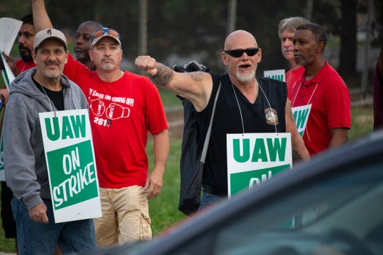 Detroit-Hamtramck Assembly GM Line worker Ralph Payne, 58, of Taylor pumps his fist as a driver honks at strikers with Local 22 take toutside of GM Detroit-Hamtramck Assembly Monday, Sept. 16, 2019.