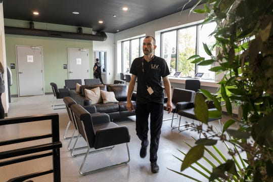 Glenn Wotherspoon, bud tender, walks through the waiting room to greet a customer at Liv, one of 2 new dispensaries opening in Ferndale, Mich., Monday, Sept. 16, 2019.