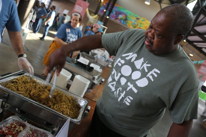 Chef Phil Jones stirs a tray of shawarma at the Make Food Not Waste event in Detroit's Eastern Market on Sunday, Sept. 8, 2019.
