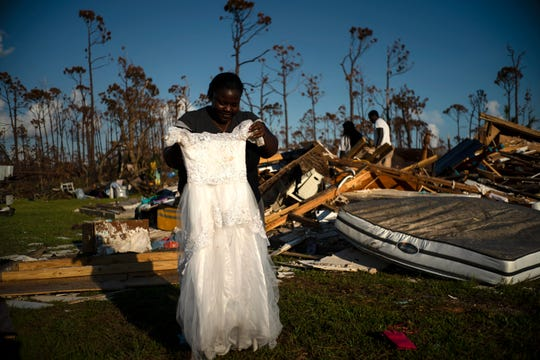 Synobia Reckley holds up the dress her niece wore as a flower girl at her wedding, as she goes through valuables in the rubble of her home destroyed one week ago by Hurricane Dorian in Rocky Creek East End, Grand Bahama, Bahamas, Sunday, Sept. 8, 2019.