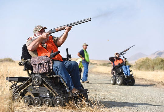 In this Nov. 16, 2018, file photo, Duane Townsend, left, shoots a pheasant at Special Friday Pheasant Hunts at Lake Success Recreation Area in Porterville, Calif. A Utah man who has been in a wheelchair for more than three decades has created a pheasant hunt for people like him who need help getting into the outdoors.