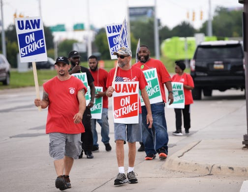 Striking UAW members walk the picket line at the main entrance of GM's Detroit-Hamtramck assembly plant Monday afternoon.