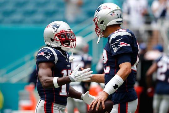 Patriots quarterback Tom Brady (12) greets wide receiver Antonio Brown (17) before Sunday's game.