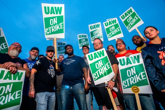 General Motors employee Bobby Caughel stands with Flint residents James Crump and Brian Bostwick as the trio, center, stands in solidarity with other General Motors employees, UAW members and labor supporters outside of the Flint Assembly Plant on Sept. 16.