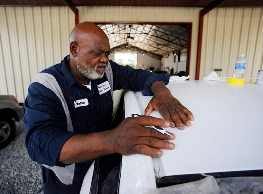 In this Tuesday, July 9, 2019 photo, Walter Porter, Mayor of Epes, Ala., works on a vehicle at his automotive body shop in Epes.  The town is still poor despite having a port along the 234-mile-long Tennessee-Tombigbee Waterway, and Porter said dreams of development from the $2 billion project remain unfulfilled more than three decades after it opened.
