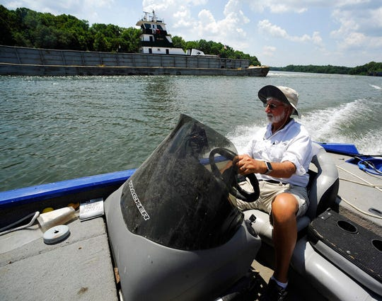In this Tuesday, July 9, 2019 photo, Fred Hansard drives a boat past a tugboat and barge on the Tennessee-Tombigbee Waterway at Demopolis, Ala. Hansard, president of the Demopolis Yacht Basin, is frustrated with uneven development along the 234-mile waterway.