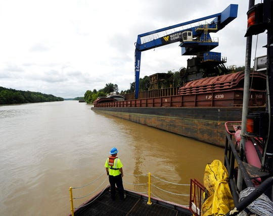 In this Monday, July 22, 2019 photo, a worker watches a crane unload scrap metal along the Tennessee-Tombigbee Waterway in Columbus, Miss. While the waterway hasn't lived up to expectations in terms of traffic or economic development in parts of Alabama and Mississippi, cities including Columbus rely on it for jobs and transportation.