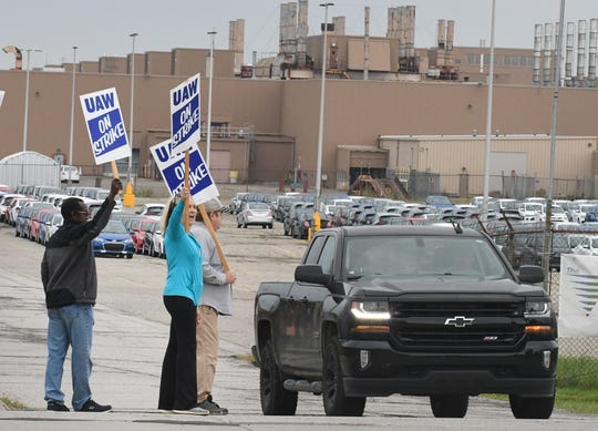 Debbie Gibson and other UAW workers react as a car honks for picketers on the south side of the GM Lake Orion Assembly plant in Lake Orion, Michigan, early Monday, Sept. 16, 2019.