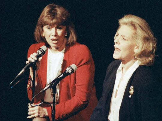 In this Dec. 13, 1990, file photo, Phyllis Newman, left, and Lauren Bacall sing during a tribute to the late conductor Leonard Bernstein, at New York's Majestic Theatre.