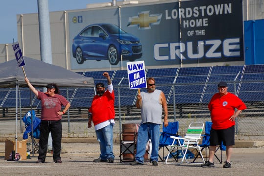 Picketers carry signs at one of the gates outside the closed General Motors automobile assembly plant, Monday, Sept. 16, 2019, in Lordstown, Ohio.
