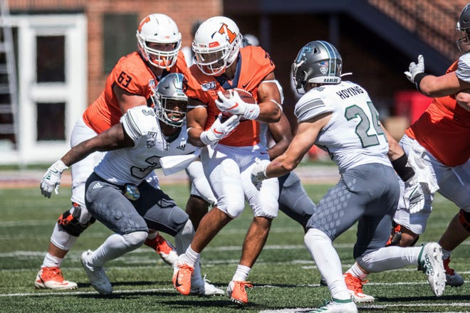 Illinois' Dre Brown is tackled by Eastern Michigan's Vince Calhoun (3) and Brody Hoying (24) in the second half.