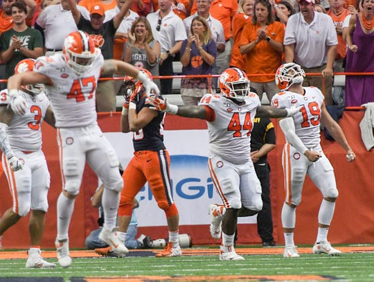 Clemson linebacker James Skalski (47), left, defensive tackle Nyles Pinckney (44), and defensive back Tanner Muse (19) celebrate a goal line stand at the two-yard-line during the third quarter at the Carrier Dome in Syracuse, New York, Saturday, September 14, 2019.