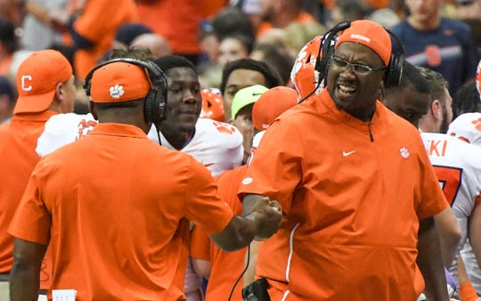 Clemson assistants Mike Reed, left, and Clemson defensive tackles coach Todd Bates celebrate a goal line stand during the third quarter at the Carrier Dome in Syracuse, New York, Saturday, September 14, 2019.