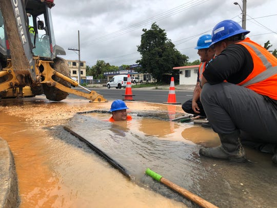 Guam Waterworks Authority trades helper Peter Quitugua, left, and other GWA employees repair a two-inch supply line off a main water line on Route 16 in Harmon in this Sept. 16 file photo.