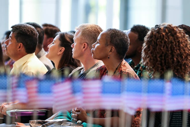 New citizens listen during a naturalization ceremony at the Indiana State Museum in Indianapolis on Monday, Sept. 16, 2019. Ninety-five people from 33 countries became United States citizens, one day before Constitution Day and Citizenship Day, September 17.