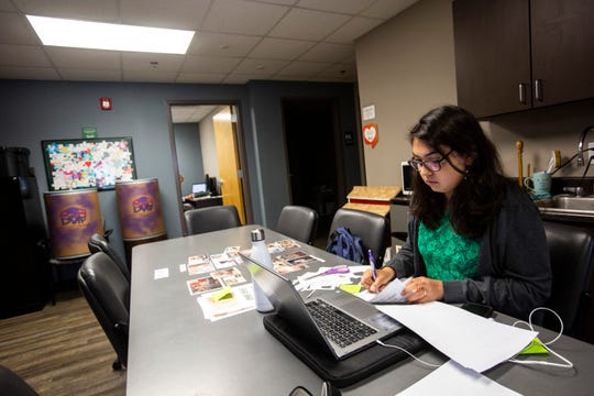 Jessica Davis, a part-time staffer at the Domestic Violence Intervention Program, works on putting together a timeline of photos, Monday, Sept. 16, 2019, at their office in Iowa City, Iowa.