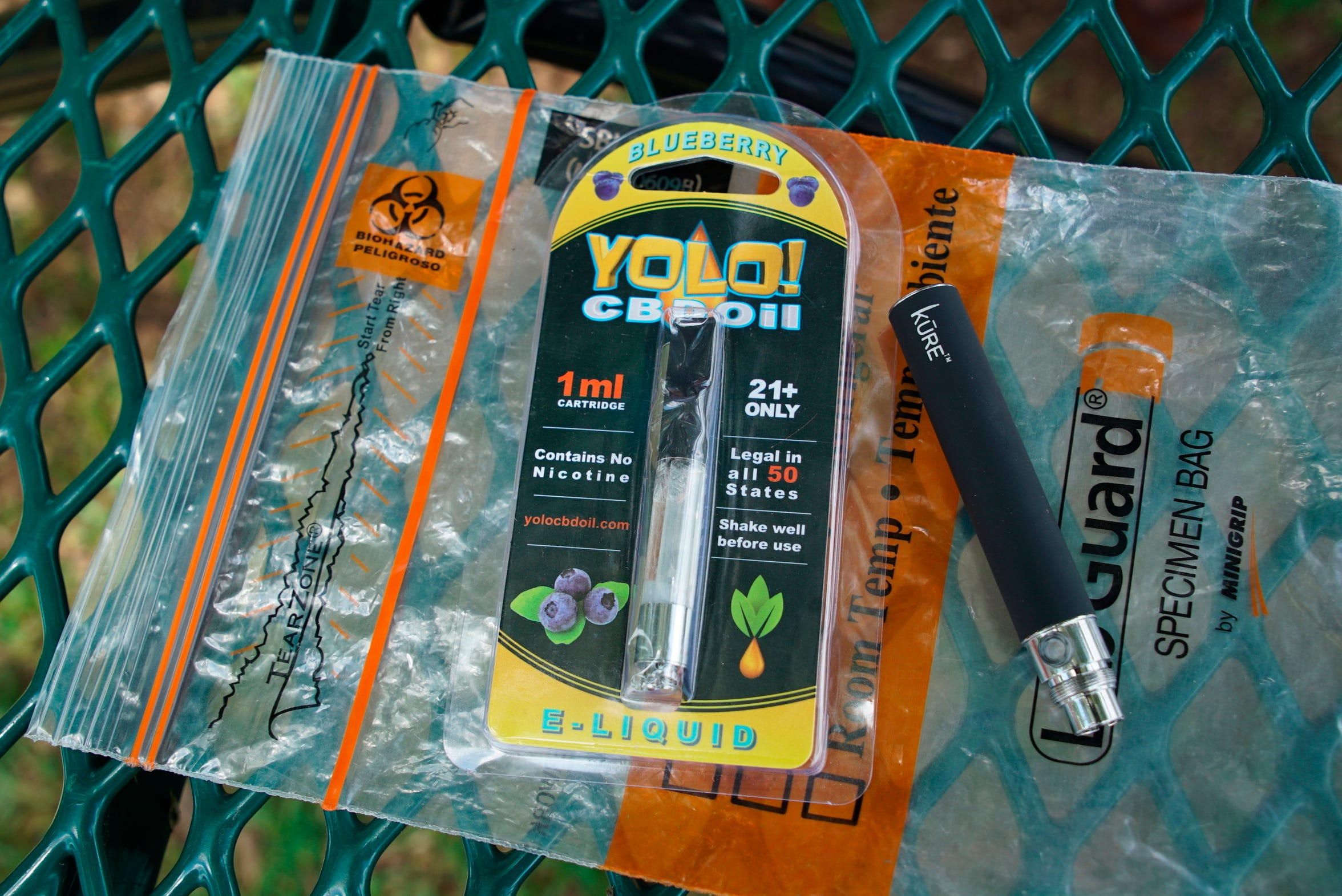 A Yolo! brand CBD oil vape cartridge sits alongside a vape pen on a biohazard bag on a table at a park in Ninety Six, S.C., on Wednesday, May 8, 2019.