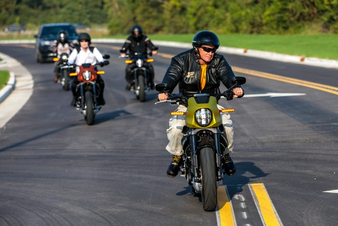 Purdue President Mitch Daniels, right, arrived on campus Monday test riding a LiveWire, Harley-Davidson's new line of electric motorcycles. Daniels, owner of a Harley-Davidson bike, took the test ride as part of the company's recruiting trip to campus on Monday, Sept. 16, 2019.