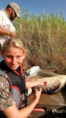 Anni Clavier gets blood on her face after harvesting one of seven alligators during a hunting trip.