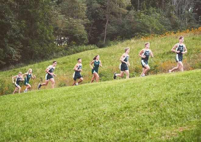 Members of the Fisher Catholic cross country team practice in preparation for the Be Moore Cross Country Invitational, which will be held at Fisher Catholic High School.